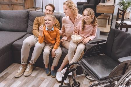 Photo for Happy family sitting on sofa and eating popcorn, wheelchair standing near by - Royalty Free Image