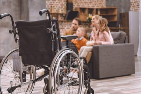 close-up view of wheelchair and happy family sitting together on sofa behind