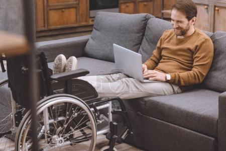 smiling disabled man putting legs on wheelchair while using laptop on sofa at home