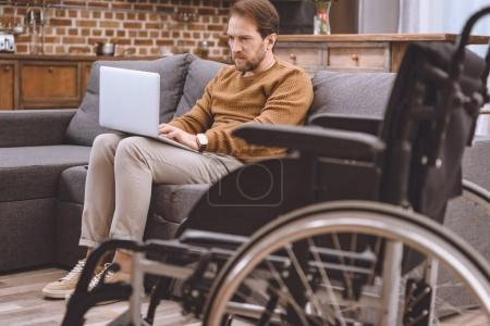 close-up view of wheelchair and disabled middle aged man using laptop on sofa at home