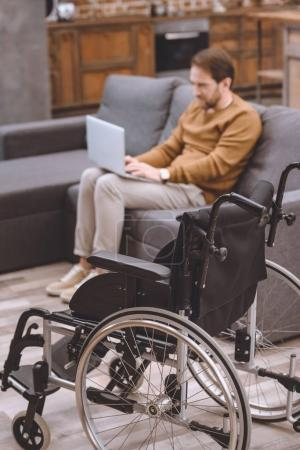 close-up view of wheelchair and disabled man using laptop on sofa at home