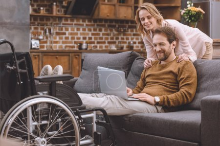 happy woman looking at disabled husband putting legs on wheelchair and using laptop at home