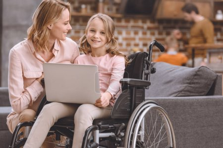 happy mother looking at cute little daughter sitting in wheelchair and using laptop at home