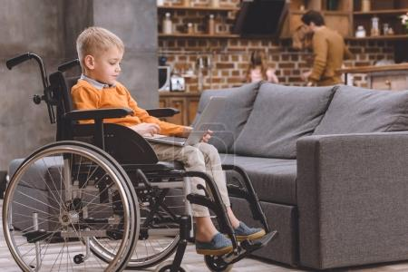 cute little child sitting in wheelchair and using laptop at home