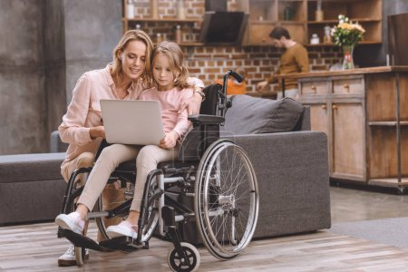 smiling mother and little daughter in wheelchair using laptop together while father and son standing behind at home
