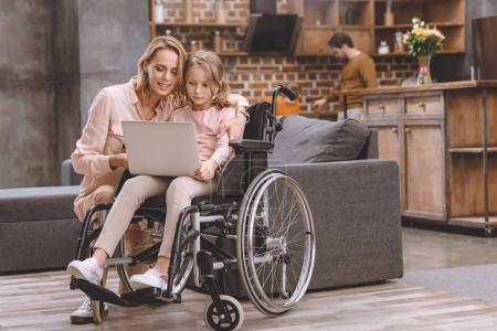 sourire, mère et petite fille en fauteuil roulant en utilisant le portable ensemble tandis que le père et le fils se tenait derrière à la maison