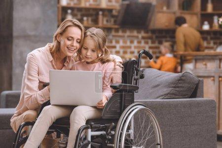sourire, mère et petite fille en fauteuil roulant avec ordinateur portable ensemble à la maison