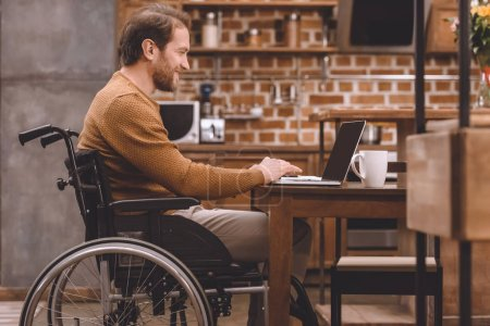 side view of smiling disabled man in wheelchair using laptop at home