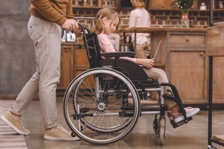 cropped shot of father carrying wheelchair with cute little daughter using laptop at home