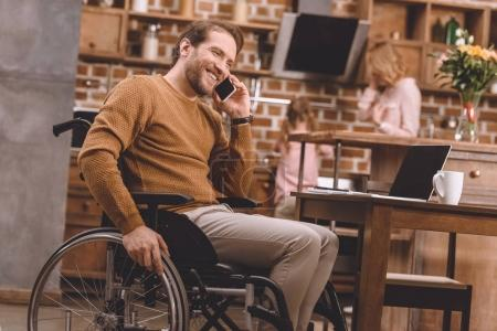 smiling disabled man in wheelchair talking on smartphone and using laptop with blank screen at home