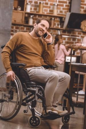 disabled man in wheelchair talking on smartphone at home