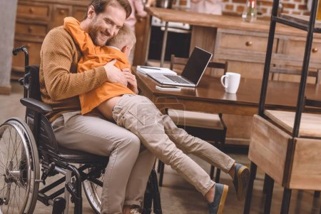 happy disabled father in wheelchair hugging with cute little son at home