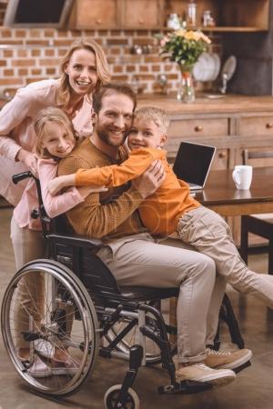 Photo pour Famille heureuse avec deux enfants et père en fauteuil roulant étreignant et souriant à la caméra à la maison - image libre de droit