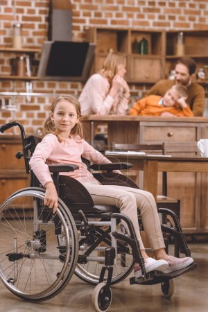 cute little girl in wheelchair looking at camera while other members of family standing behind at home