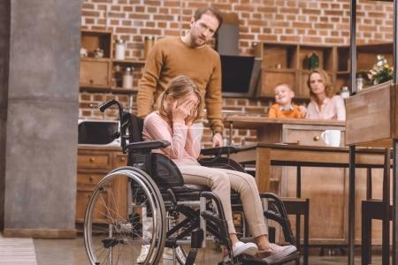 father looking at little daughter sitting in wheelchair and closing eyes with palms at home