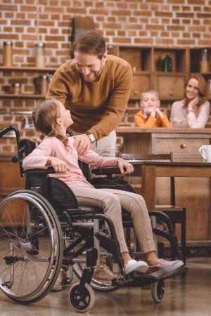 father and cute little daughter in wheelchair smiling each other at home