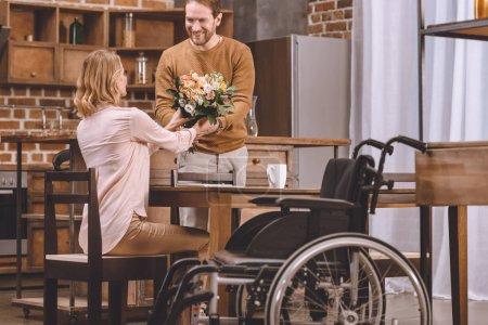 homme présentant des fleurs à une femme handicapée et fauteuil roulant debout près souriant