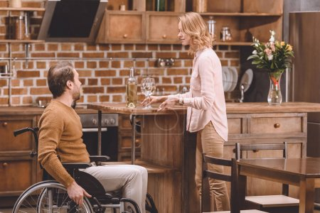 side view of woman with wine bottle and glasses looking at disabled man sitting in wheelchair at home