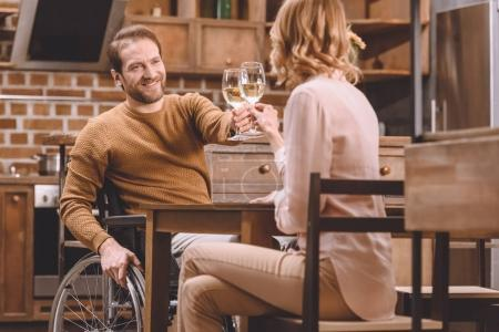 woman and smiling man in wheelchair clinking wine glasses at home