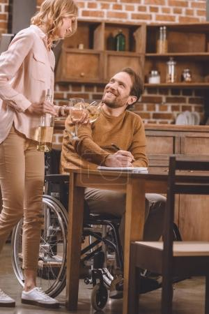 cropped shot of smiling woman holding wine glasses and bottle while husband in wheelchair taking notes at home