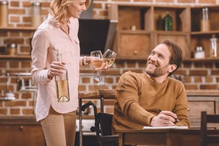 smiling woman holding wine glasses and bottle while disabled husband in wheelchair taking notes at home