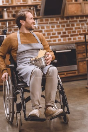 smiling disabled man in wheelchair holding pan with raw spaghetti and looking away at home