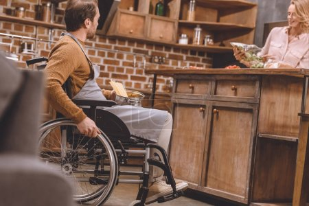 selective focus of woman with disabled man in wheelchair cooking dinner together at home