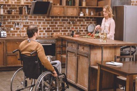 femme avec un homme handicapé en fauteuil roulant cuisson dîner ensemble à la maison