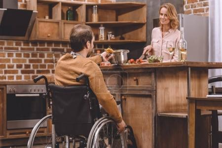 smiling woman with man in wheelchair cooking dinner together at home