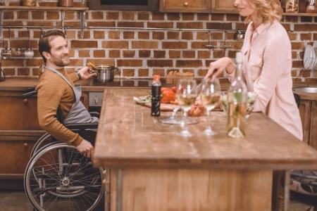 recadrée tir de femme avec homme cuisson dîner de fauteuil roulant ensemble à la maison
