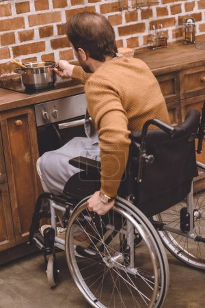 back view of disabled man in wheelchair holding pan while cooking at home