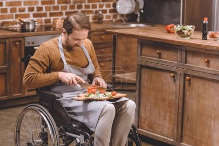 high angle view of disabled man in wheelchair cutting vegetables at home