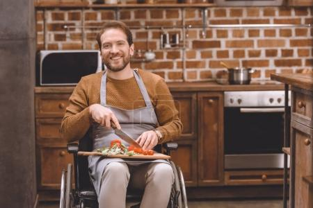 disabled man in wheelchair cutting vegetables and smiling at camera at home