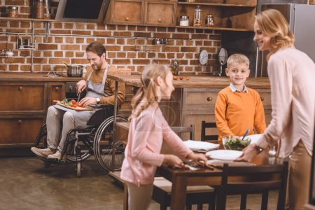 Photo for Cute little kids with mother serving table for dinner while disabled father in wheelchair cutting vegetables behind - Royalty Free Image