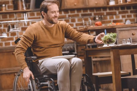 smiling disabled man in wheelchair holding glass bowl of vegetable salad at home