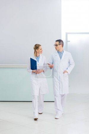 two doctors in white coats with diagnosis talking in hospital corridor