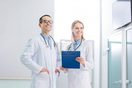 two cheerful doctors in white coats with stethoscopes and diagnosis standing in clinic
