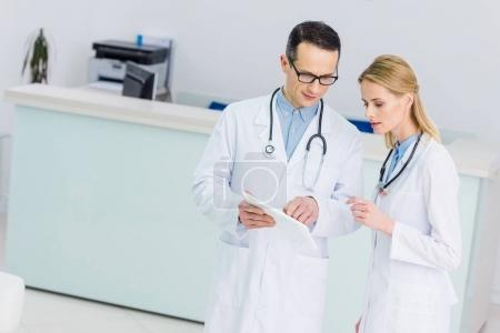two doctors in white coats with tablet discussing diagnosis in clinic