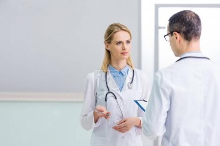 two doctors in white coats discussing diagnosis in clinic