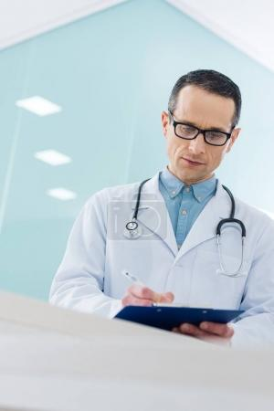 confident doctor in white coat with stethoscope writing diagnosis in hospital