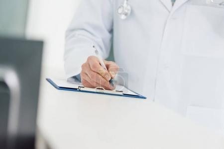 Photo pour Vue recadrée du médecin en blouse blanche écriture diagnostic à l'hôpital - image libre de droit
