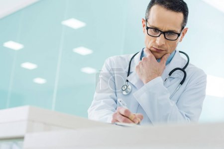 thoughtful doctor in white coat with stethoscope writing diagnosis in hospital