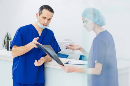 two surgeons discussing x-ray and diagnosis in hospital