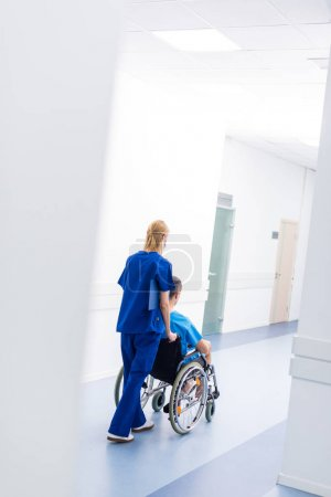rear view of surgeon and upset patient in wheelchair in hospital corridor