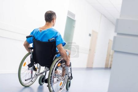 back view of male patient in wheelchair in hospital