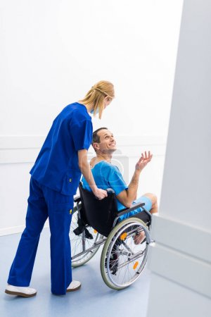 surgeon talking with smiling male patient in wheelchair in hospital corridor