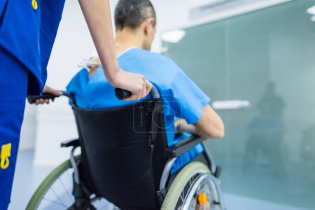 rear view of surgeon and male patient in wheelchair in hospital corridor