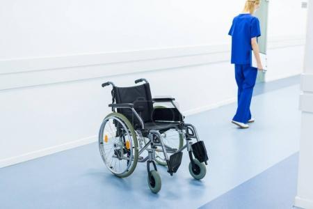 female surgeon in hospital corridor, wheelchair on foreground