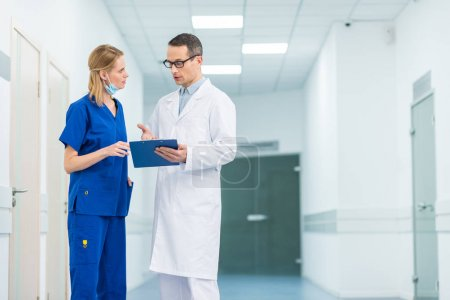doctor in white coat and female surgeon discussing diagnosis in hospital