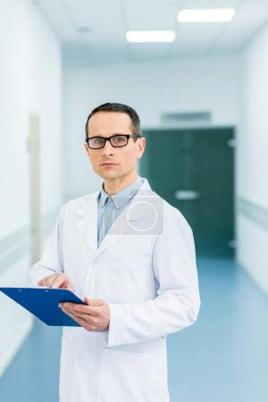male doctor in eyeglasses and white coat holding diagnosis in hospital